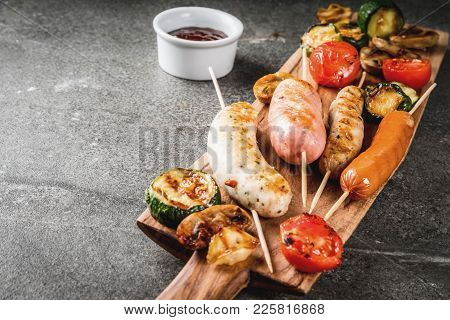 Barbecue. Assortment Of Various Grilled Meat Sausages, With Vegetables Bbq - Mushrooms, Tomatoes, Zu