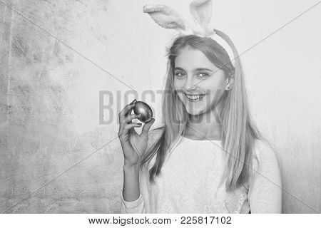 Happy Easter Girl In Pink Bunny Ears With Golden Egg In Hand, Has Long Blond Hair, Smiling Face On Y