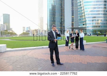 Businessman Speaking By Smartphone Outside, Keeping Blue Document Case With Employees In Background.