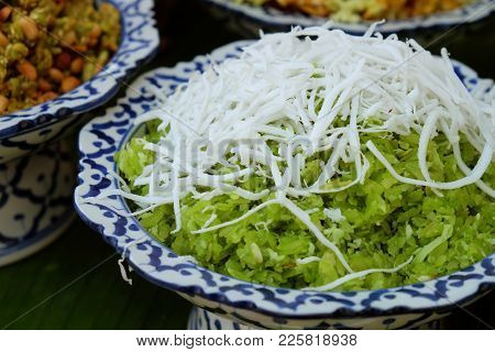 Green Pounded Unripe Rice With Sliced Coconut On The Top In White And Blue Ceramic Tray With Pedesta