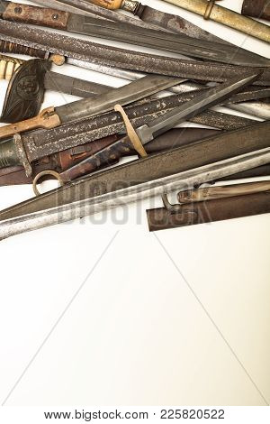 Collection Of Vintage Weapons , Old Swords And Daggers Forming A Side Border Over White With Copy Sp