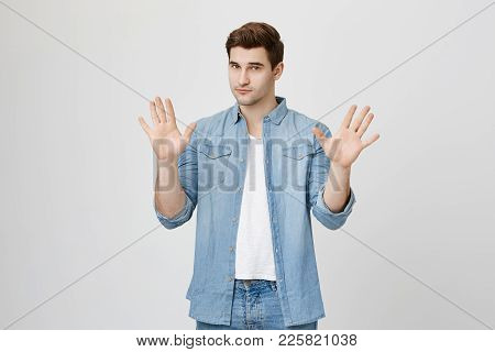 Body Language. Serious Confident Unshaven Man In Denim Shirt Posing Against Studio Wall, Keeping Han