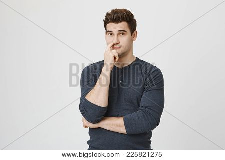 Dark-haired Man With Stubble With Finger In His Nose, Looks Pensively At Camera, Isolated Against Gr