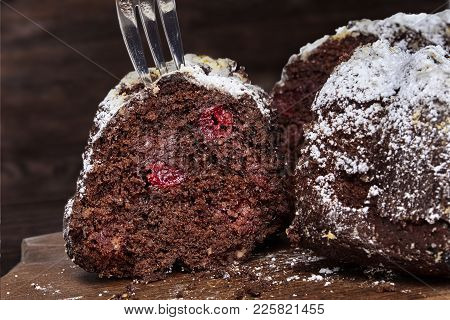 Chocolate Cake With Sour Cherries And Wallnuts Cut Into Several Pieces On The Wooden Rustic Backgrou