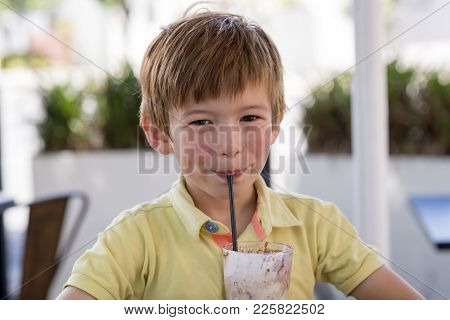 Head Portrait Of Lovely And Sweet Young Kid 7 Or 8 Years Old In Yellow Shirt  Enjoying Happy Drinkin