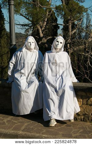 Two Spooky White Ghost With Black Eyes Sitting In The Wall Of Castiglion Fibocchi. Halloween Or Carn