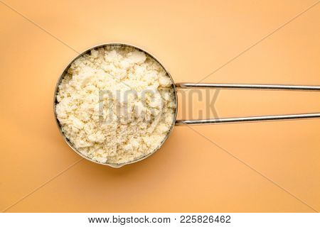 measuring metal scoop of whey protein powder against beige background