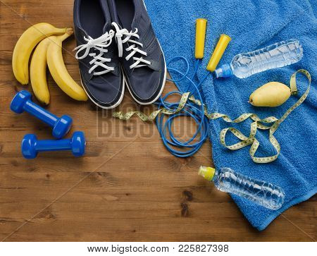 Fitness Concept With Sneakers Dumbbells Skipping Rope Measure Tape Towel Bottle Of Water Pear And Ba