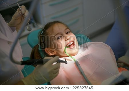Little Girl At Dentist Office, Getting Ready For A Caries Treatment. Prevention, Pediatric Medical C