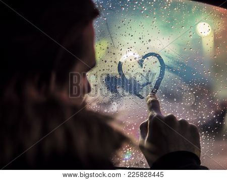Side View Of Romantic Man Drawing Heart On Steamy Car Window Against Night Lights.