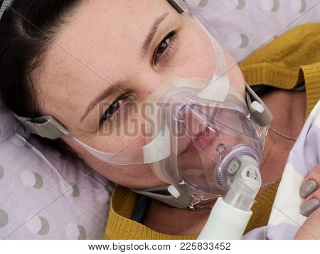 woman in a hospital with an oxygen mask on her face