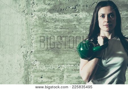 Muscular Young Woman Holding Kettlebell With Her Hand On Her Shoulder, Sport Concept