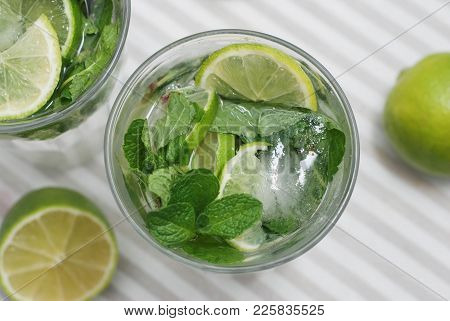 Glass Of Mojito Cocktail With Fresh Lime And Mint On A Rustic Fabric