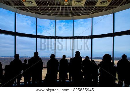 A Group Of People Looking Out A Window At A Runway And Airport.