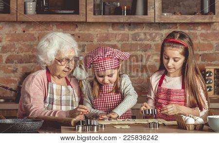Little granddaughters help granny to bake cookies