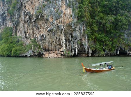 Thai Longtail Boat Near Limestone Cliffs In Phang Nga Bay