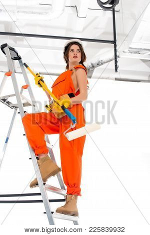 brunette workwoman in overalls and hardhat holding painting roller while standing on ladder poster