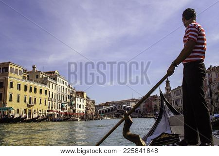 Gondolier Rowing On The Grand Canal And In The Background The Bridge Of Riu Alto