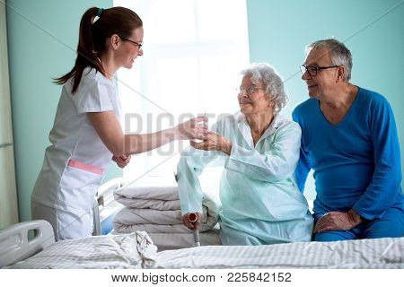 Nursing Home, Young Careful Nurse Brings Water To Old Woman At Nursing Home