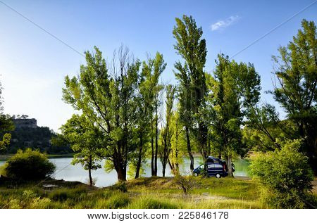 Camper van parked on a lake, campsite in the nature, freedom concept