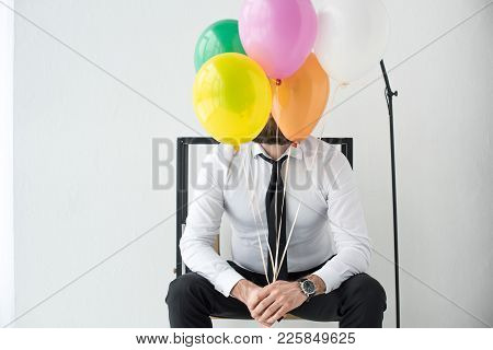 Obscured View Of Businessman With Colorful Balloons Sitting On Chair