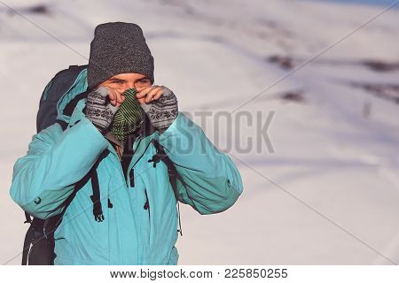 Man, Covering His Face With A Scarf, Wearing Grey Hat And Blue Anorak, Doing Outdoor Activity In Win