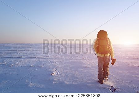 Mountaineer Walks Up Hill On A Glacier. Rear View, Backlight, Large Copy Space On The Left. He Is Ho