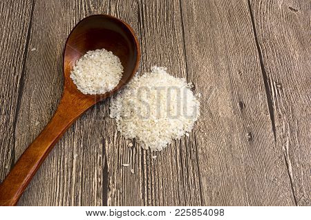 Wooden Spoon With Rice Grains, Natural Foods. Rice Grains In A Wooden Spoon