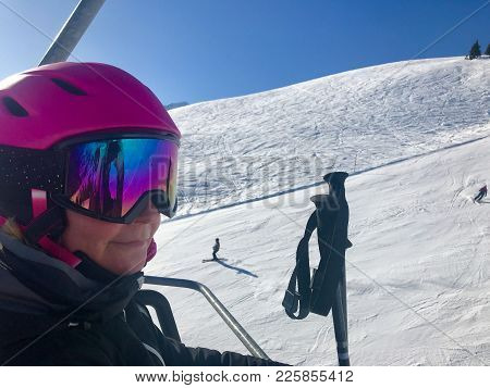 Female Skier In Skilift Wearing Helmet And Goggles