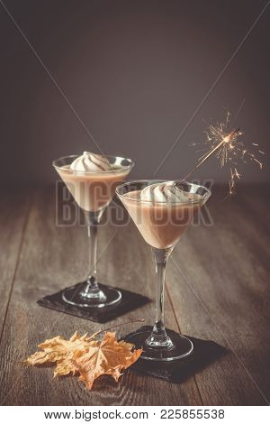 Two glasses of Irish cream liqueur with sparkler and autumn leaves