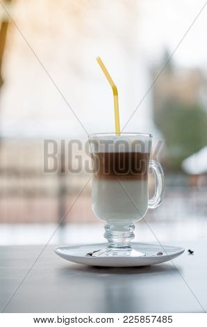 Latte On The Table In The Cafe Layer Of Milk, Coffee And Milk Foam In Classic Latte Cup, With Yellow
