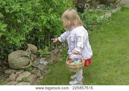 Little Girl Hunting For Easter Egg In A Spring Garden On Easter Day