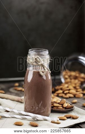 Organic Chocolate  Almond Milk In A Glass Bottle With Whole Almonds Spilled Over A Rustic Wooden Tab