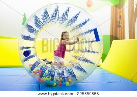 Child Play In Roller Wheel. Kids On Trampoline.