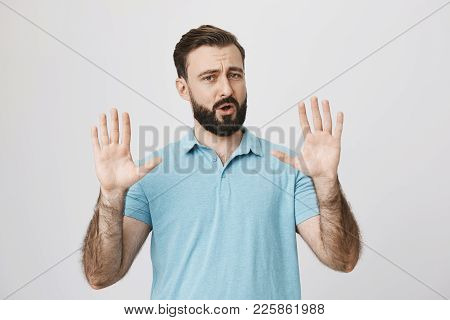 Portrait Of Attractive Mature Man Showing Hold On Gesture With Raised Palms And Opened Mouth, Standi