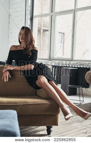 Looks Perfect. Attractive Young Woman In Elegant Black Dress Keeping Legs Crossed At Knee And Lookin