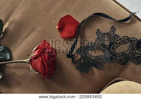 Feel The Passion. Close Up Top View Of Single Red Rose And Black Mask Lying On The Sofa
