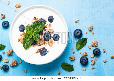 Greek Yogurt Granola And Blueberries On Blue Table. Top View With Copy Space.