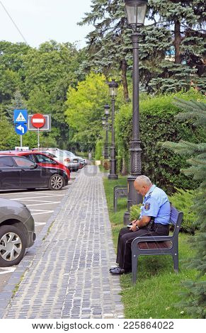 Brasov, Romania - July 25, 2017: Police Officer Is Writing Down Something On A Bench In Brasov, Roma
