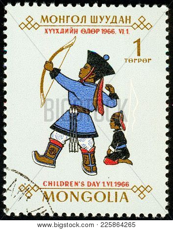 Ukraine - Circa 2018: A Postage Stamp Printed In Mongolia Shows A Child Shooting With An Arrow From