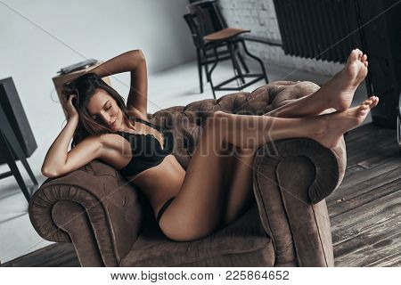 Total Relaxation. Attractive Young Woman In Underwear Keeping Hands In Hair While Sitting In The Arm
