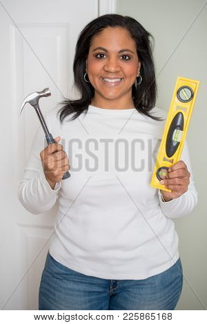 Woman with a hammer repairing her house