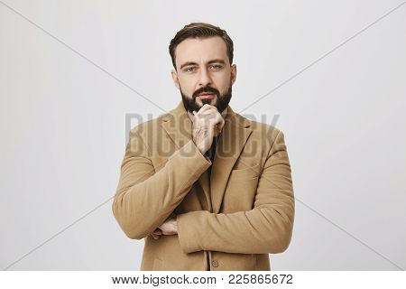 Bearded Man In Coat Looking Interested In Something Holding His Hand On Chin Looking At Camera Over