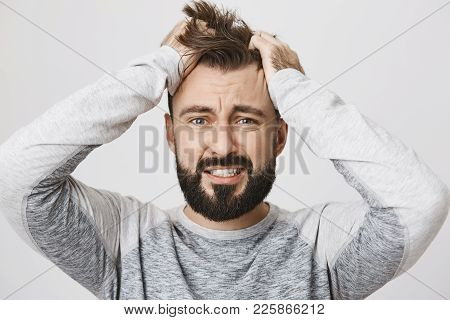 Portrait Of Depressed Bearded Guy Feeling Pressure, Grabbing Hair With Hands And Expressing Devastat