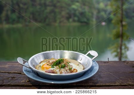 Thai Style Omelet In Plate On The Wooden Table With The River View On Behind