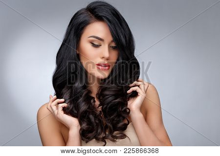 Beautiful Face Of Young Woman With Clean Healthy Curly Hair Close Up Isolated On Gray Background. Be