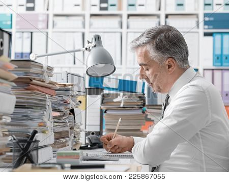 Businessman Working In The Office And Piles Of Paperwork
