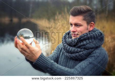 Handsome Blond Man In Front Of Lake Holding A Glass Ball