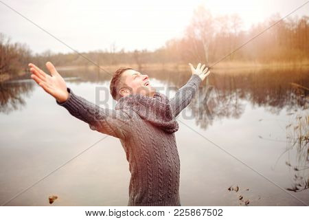 Blond Man Outdoors In Front Of Lake Spreading His Arms