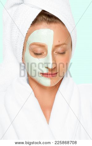 Treatment In Spa Salon. Beautiful Young Woman With Cosmetic Clay Mask On Face. Faded Pastel Color